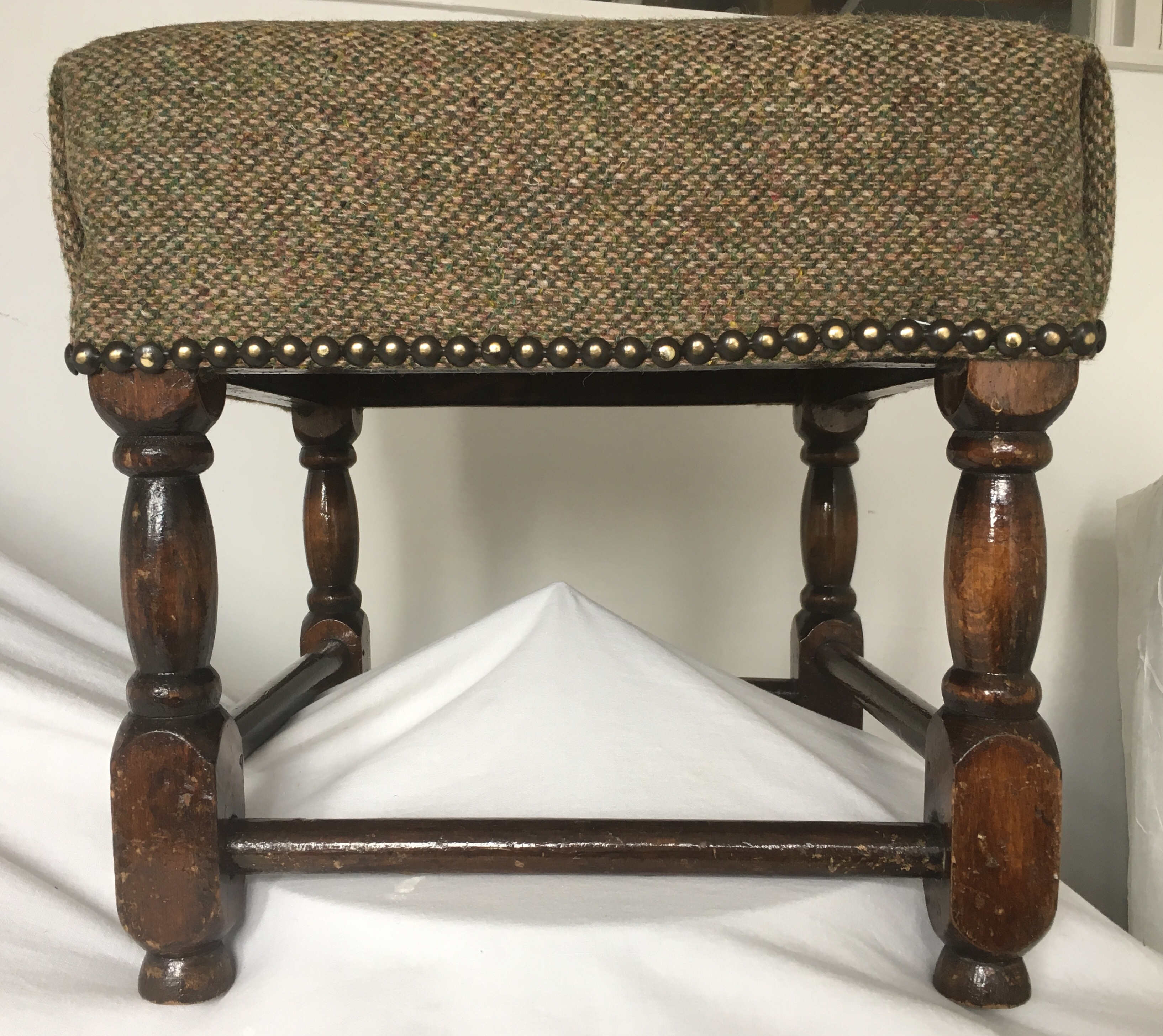 Refurbished footstool for client to order using tweed cloth and reupholstery materials.